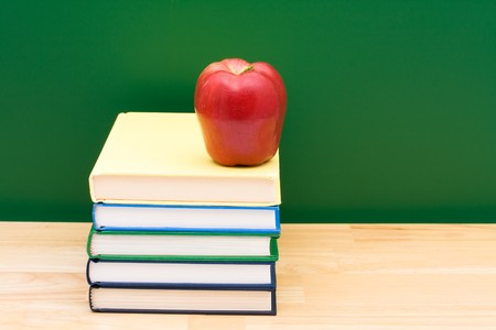 Stack of  books with an apple in front of the chalkboard, School Days