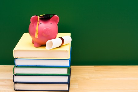 Stack of blue books with a piggy bank in front of a chalkboard, Costs of an education