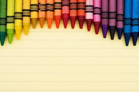 Kleurrijke crayons op een vel gelinieerd papier, educatieve achtergrond Stockfoto