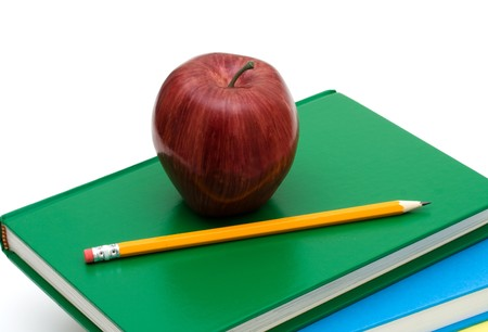 A pencil and an apple on a stack of books isolated on a white background, school work Stock Photo - 7395942