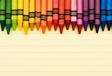Colorful crayons on a sheet of lined paper, Educational background Stock Photo