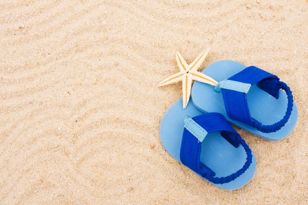 A starfish and a pair of baby's sandals sitting on a sand background, beach baby photo