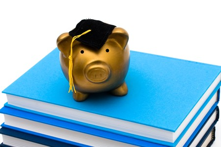 scholarship: Stack of blue books with a piggy bank isolated on white, Costs of an education  Stock Photo