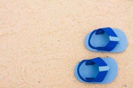 A starfish and a pair of baby�s sandals sitting on a sand background, beach baby photo