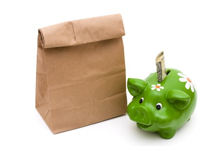 money packs: A green piggy bank with a brown paper bag isolated on a white background, saving your lunch money