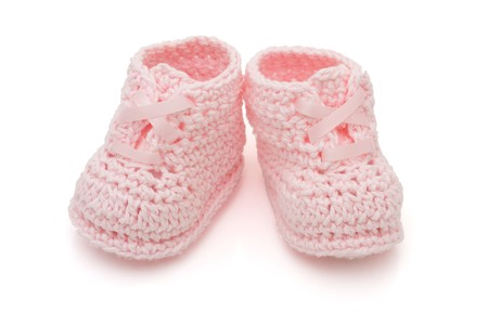 Handmade pink baby booties isolated on a white background Stok Fotoğraf - 7590427