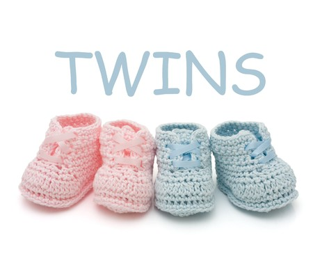 Handmade pink and blue baby booties for twins isolated on a white background
