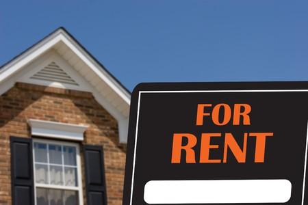 for rent sign: A black and orange for rent sign with a brick house in background
