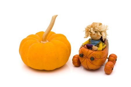 A pumpkin with a little scarecrow driving a pumpkin isolated on white, autumn  photo
