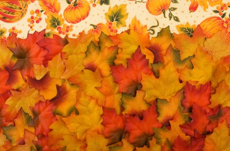 Fall leaves with a pumpkin border at the top, autumn background photo