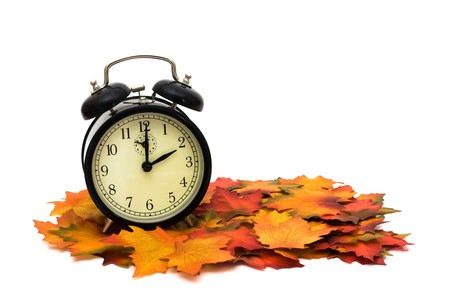 Retro black alarm clock on fall leaves, Fall Time change 版權商用圖片