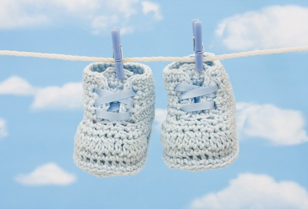 Retro hand made baby booties on a sky background photo