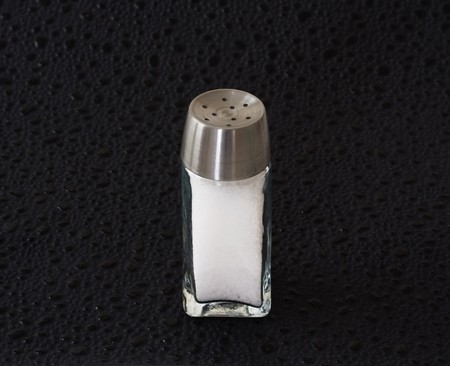 Salt shaker full of salt on a black background Stock Photo - 7988428