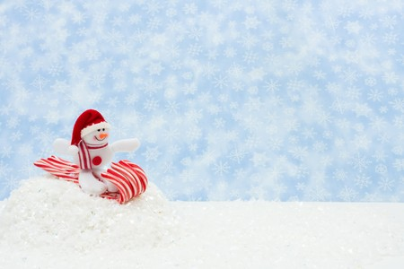 snowman on a candy cane sled with snow, Snowman having fun photo