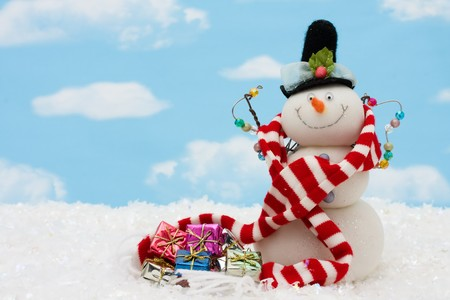 Snowman wearing scarf on blue sky background, merry Christmas