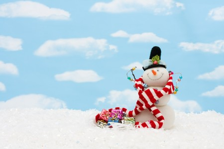 Snowman wearing scarf on blue sky background, merry Christmas  photo