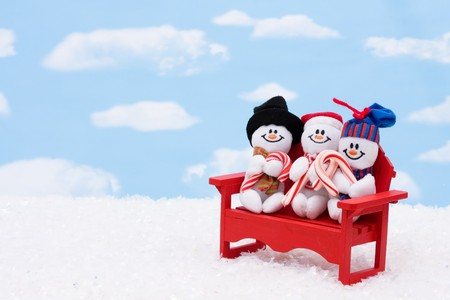 Three snowmen sitting on a red bench with a sky background, Christmas Time photo