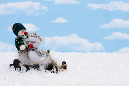Two snowmen sitting on a sleigh with a sky background, snowman