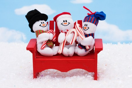 Three snowmen sitting on a red bench with a sky background, winter time photo