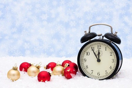 Red and gold glass Christmas balls with an alarm clock on a snowflake background, Christmas Time Stock Photo - 8199452