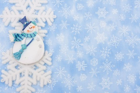 A snowflake and a snowman on a blue snowflake background, Christmas Time photo