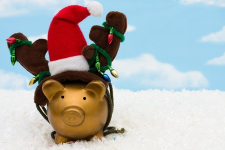 christmas savings: A piggy bank with a santa hat, reindeer antlers and christmas lights on a sky background, christmas savings Stock Photo