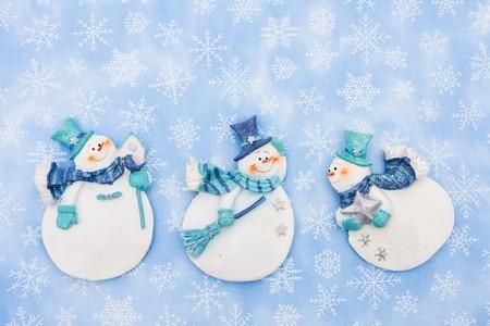Three snowmen on a snowflake background, Winter Time photo