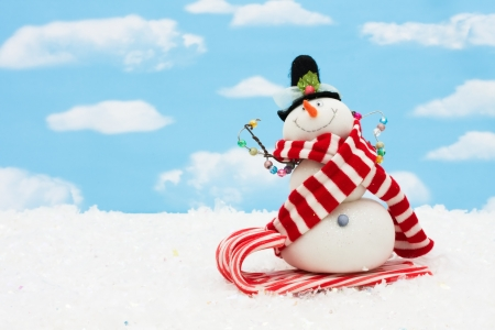 Snowman on a candy cane sleigh on a blue sky background, snowman having fun Stock Photo