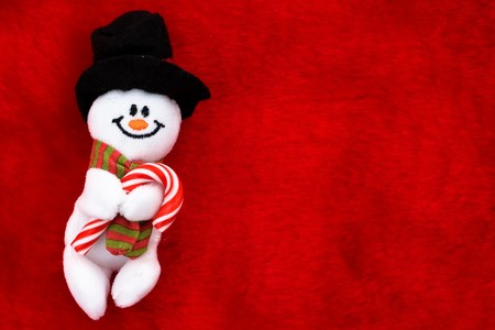 A snowman with a candy cane on a red background, Christmas Time Stock Photo - 8215625