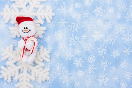 A snowflake and a snowman on a blue snowflake background, Christmas Time Stock Photo - 8215633