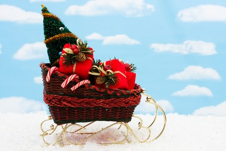 A wicker sleigh with presents in it with a sky background, Santa sleigh Stock Photo - 8215642