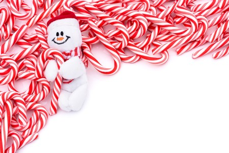 Mini candy canes making a border on a white background, Candy cane border Imagens