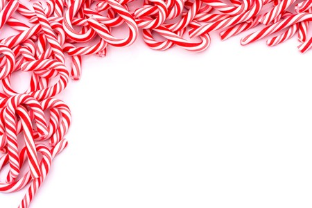 Mini candy canes making a border on a white background, Christmas Candy cane Imagens