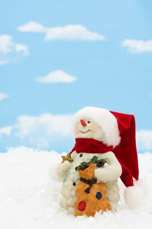 A snowman on a blue sky background, winter time photo