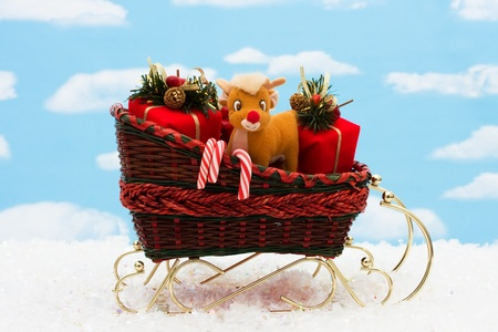 A wicker sleigh with presents in it with a sky background, Santa sleigh photo
