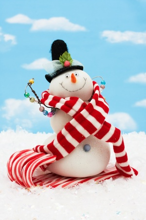 Snowman  with scarf on a blue sky background, winter time