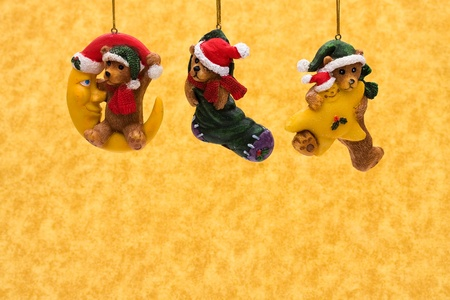 Three teddy bear Christmas tree ornaments on a yellow background, Chritmas Time photo