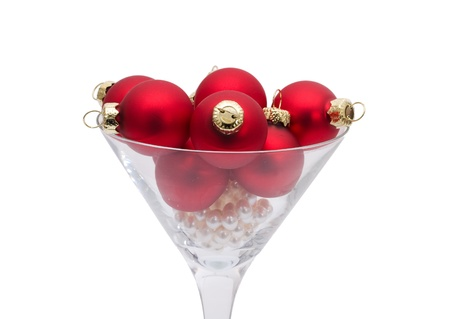 holding a christmas ornament: Red christmas balls in a martini glass isolated on a  white background, Christmas time