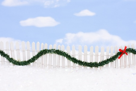 picket fence: White picket fence with green garland and red bow, merry Christmas