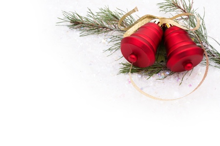 Red bells with a gold ribbon on a snow background, Christmas time
