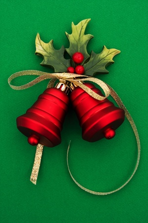 berry: Red bells with holly and berries on a green background, Christmas Time Stock Photo
