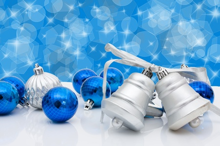 Blue christmas balls and bells on a blue sparkle background, christmas time photo
