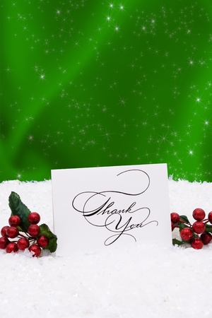 A thank you card sitting on snow with a green background photo
