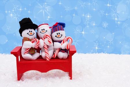 Three snowmen sitting on a bench with a blue background, Snowmen having fun photo