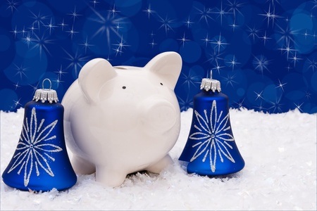 christmas savings: Blue christmas bells with a piggy bank on a snow and blue background, christmas  savings  Stock Photo