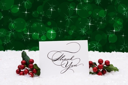 A thank you card sitting on snow with a green background, Christmas time photo