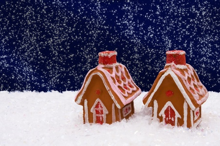 Gingerbread house on snow with a night sky background, winter time photo