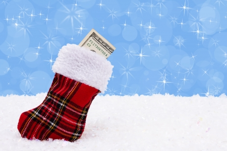 christmas sock: A stocking with a one hundred dollar bill on a snow background, Christmas Time Stock Photo