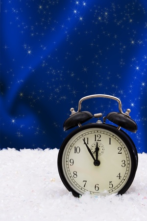 A black vintage face clock sitting on snow background, winter time photo