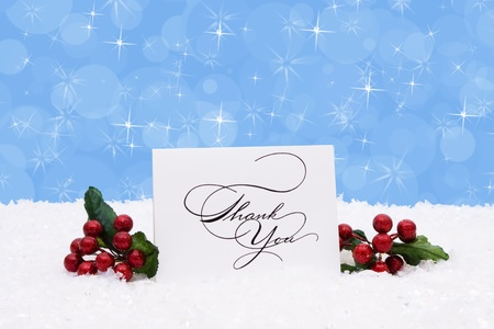 A thank you card sitting on snow with a blue background, Christmas Time photo